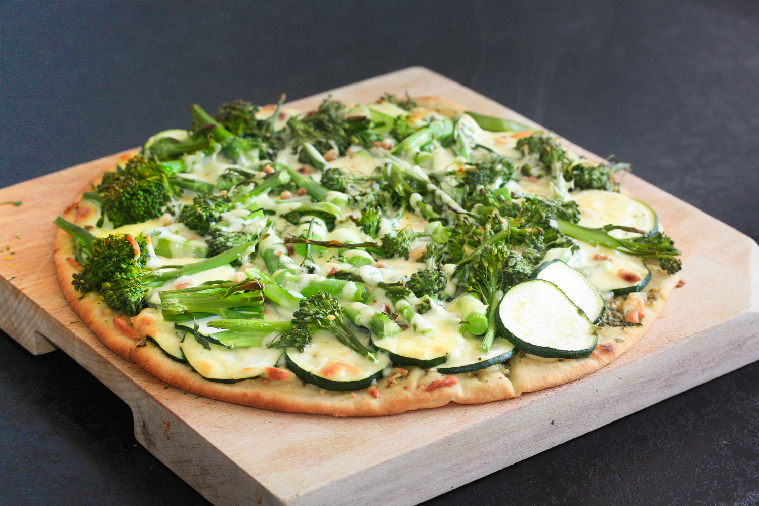 Broccolini and pesto pizza with rocket and pine nuts